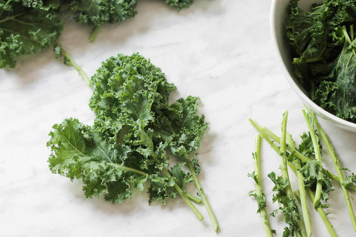 Kale leaves on marble counter top with stems removed