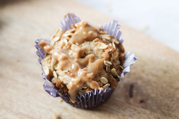 Freshly baked apple muffin in purple muffin liner on wooden cutting board
