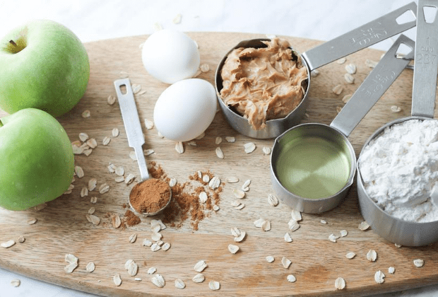 Oval wood cutting board with apples, peanut butter, eggs, flour, oil and spices for making muffins