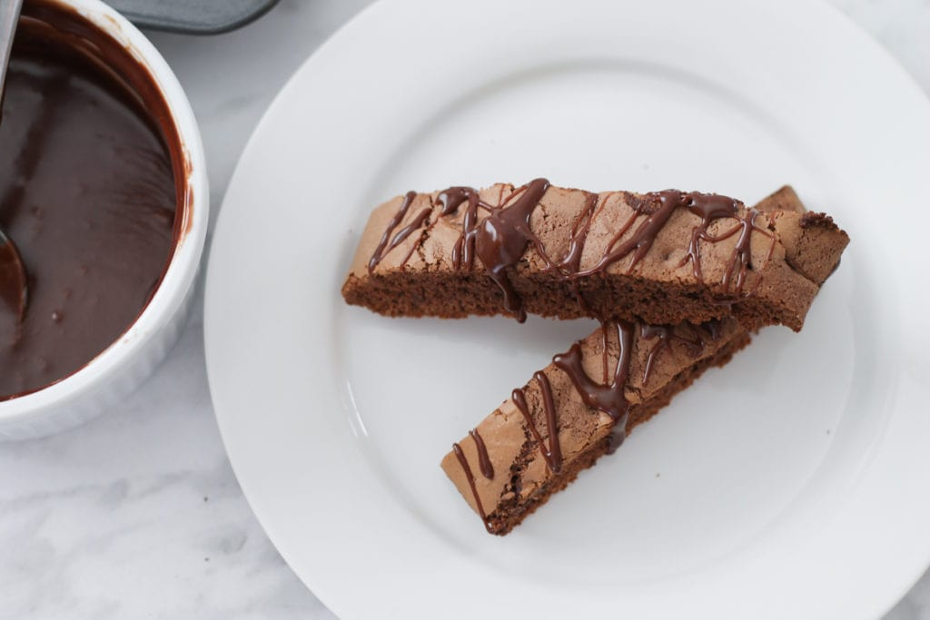 Small white plate with two stacked biscotti cookies and a ramekin of Nutella drizzle to the side.