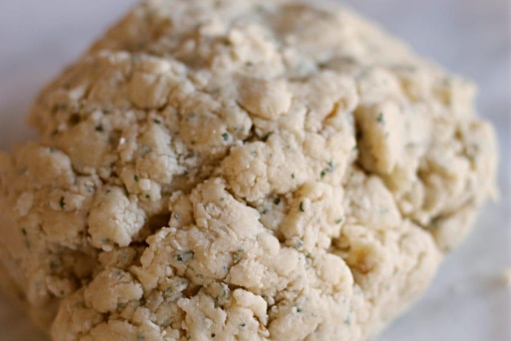 Dough ball for cheese scones on countertop.