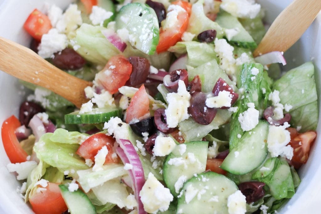 Large white ceramic bowl of Greek salad with wooden salad servers.