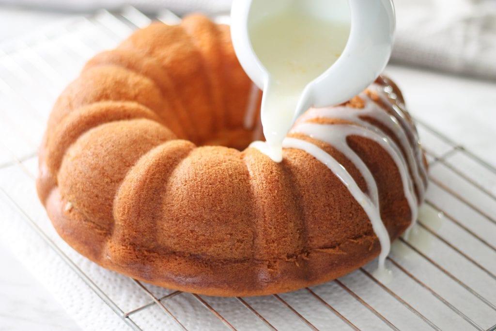 Lemon bundt cake being drizzled with fresh lemon glaze over a metal cooling rack.