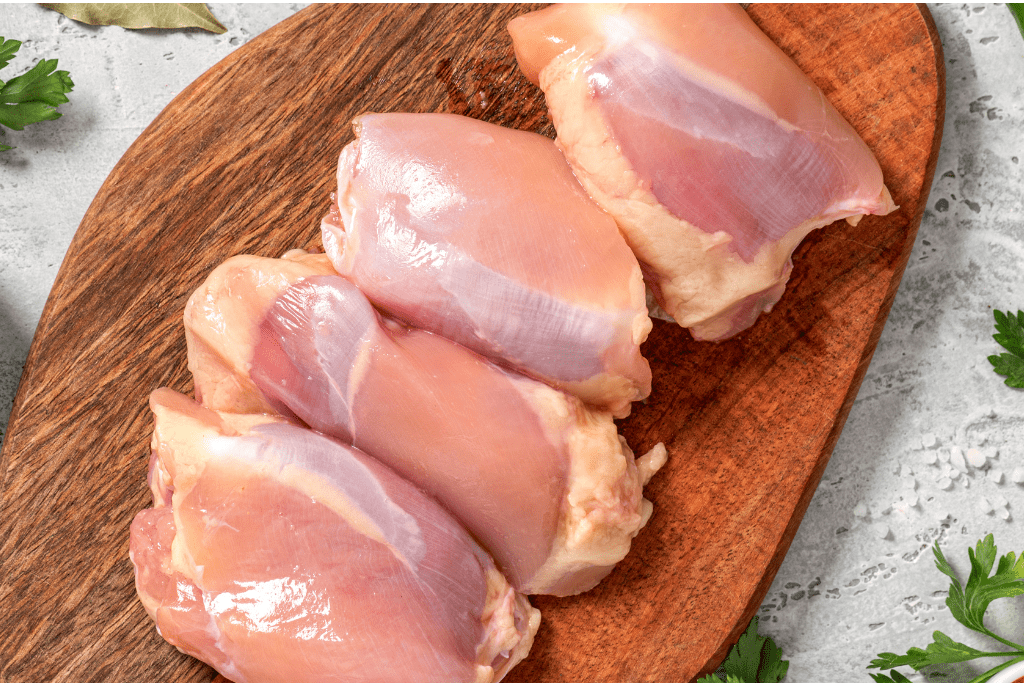 Chicken thighs on wooden cutting board.