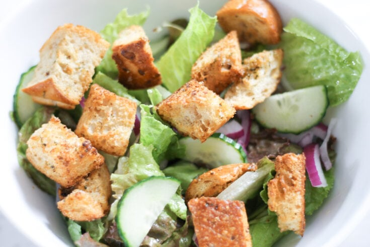 Bowl of green salad topped with croutons.
